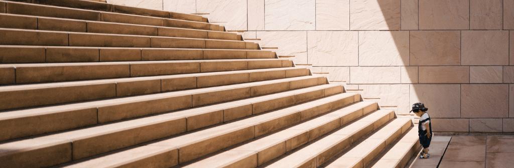 Een kind die trap te hoog vind om alleen te nemen
