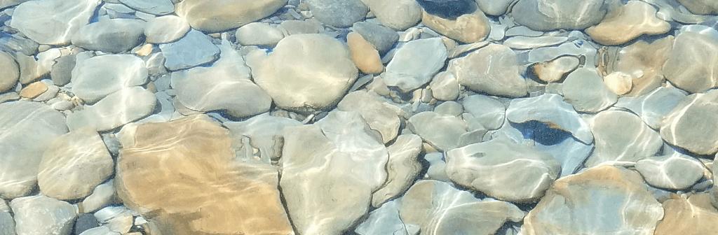 Frisse helder water waar stenen met verschillende kleuren in liggen